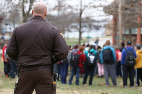 "Sheriff Jason King watches over the students gathered in the Free Speech Zone during the Campus Ministry USA's demonstration Monday. King said he wasn't asked to go watch over the event, but felt ""they might need me out here."""