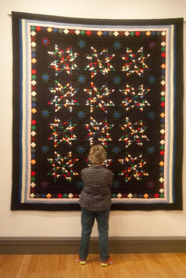 Jeanne Douthitt examines the quilt named Amish Sparkling Star at the Quilting in Community: A Celebration of a Southern Indiana Amish Tradition exhibit in the Pace Gallery on Sunday.