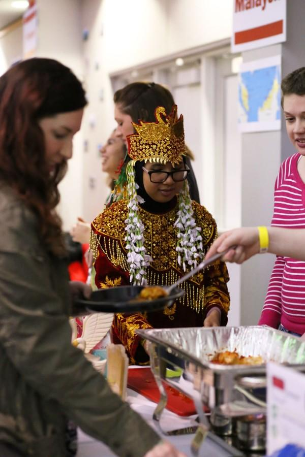 Endah Rosa, a sophomore biology major, helps out at the Indonesian booth dressed in traditional Indonesian attire at the International Food Expo Friday in Carter Hall.