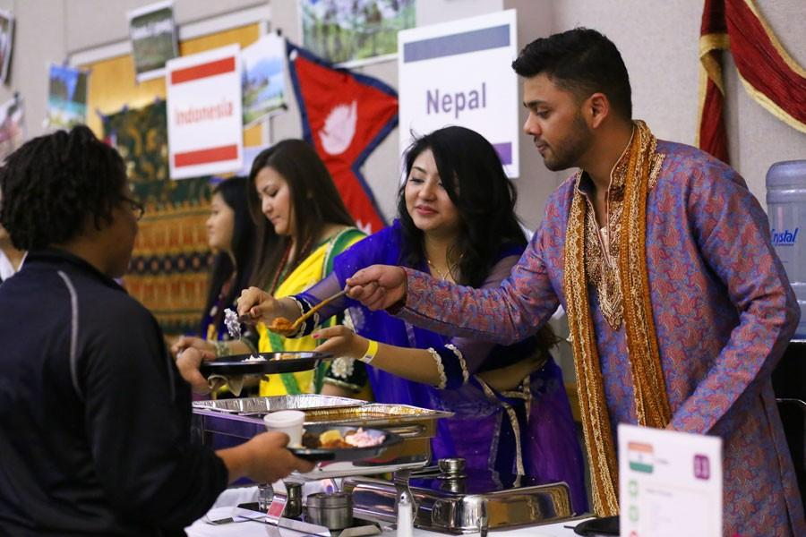 Representing India, Britee Piya, a sophomore biology major, and Mario Jaiswal, a senior computer information systems major, pass out buttered chicken to guests at the International Food Expo Friday in Carter Hall.