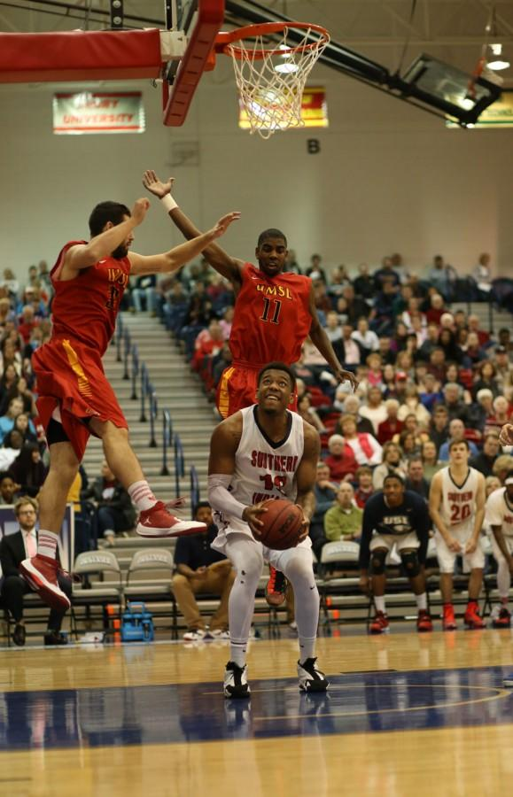 Junior forward T.J. Tisdell fakes out members of the University of Missouri-St. Louis men's basketball team during the homecoming game in the PAC Saturday. Tisdell finished the game with 20 points putting USI in the lead with a final score of 86-76.