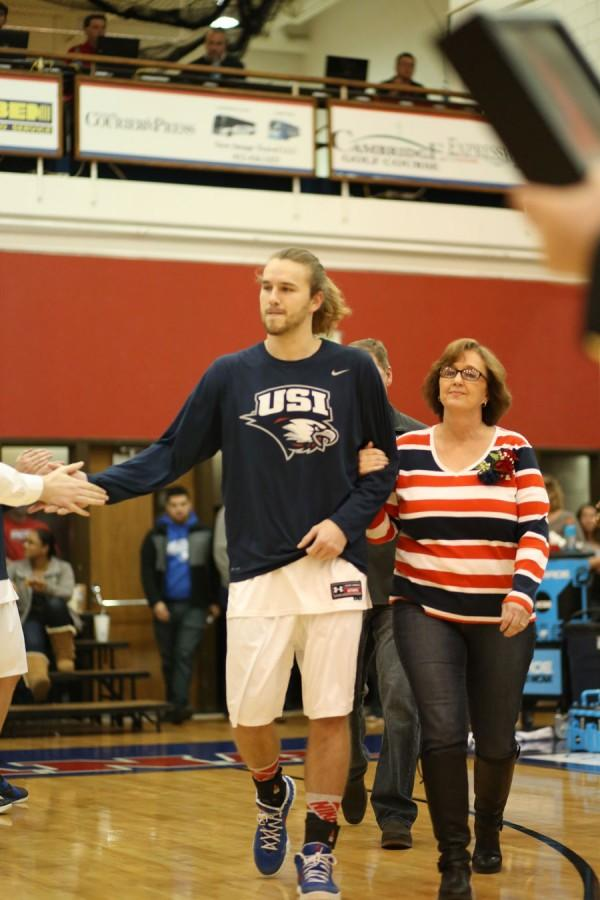 Senior forward Shane Seniour walks with his mother, Dana Seniour, after being announced onto the court for the team's senior night.