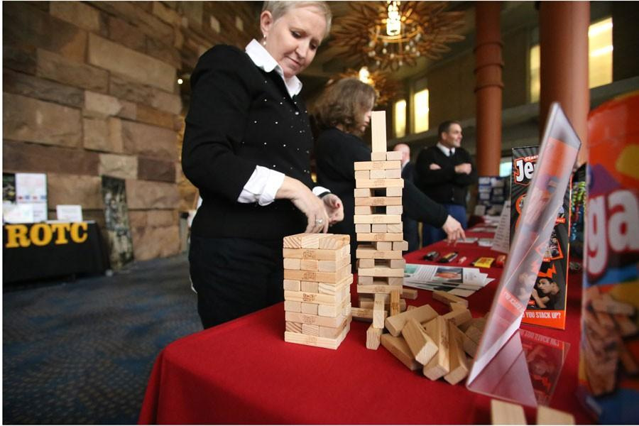 Director of Corporate Partnerships Charmaine McDowell sets up Jenga, which she uses for team building during the interactive fair for the Celebration of Engagement Tuesday at the Performance Center. This was the second year for the Celebration of Engagement which aims to inform faculty on the partnerships and interactions that go on as a result of Outreach and Engagement.