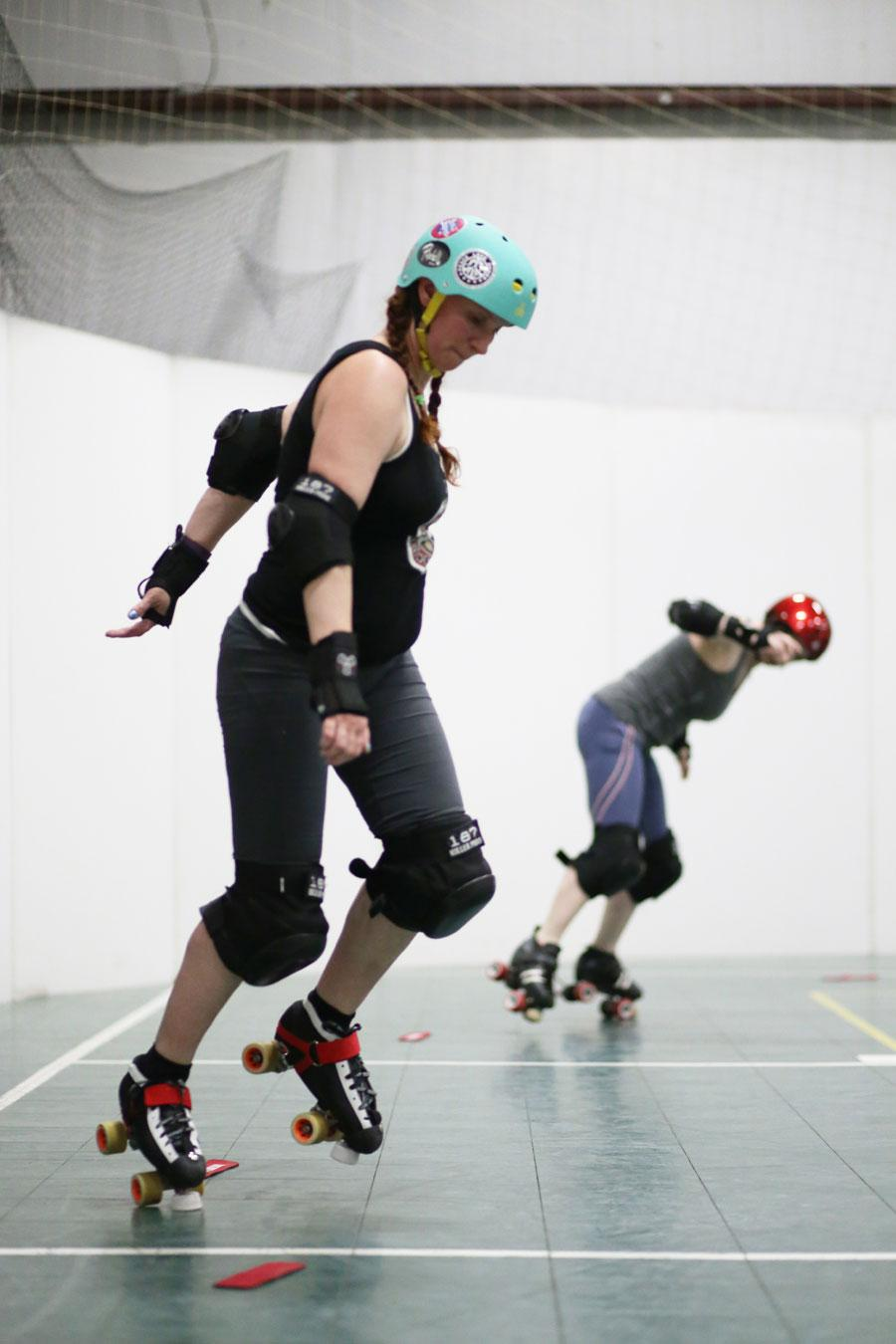 USI alumnae Jolie DeVries and Cassie Kahn work on drills during practice for the Demolition City Roller Derby League Tuesday at the Metro Sports Center in Evansville.