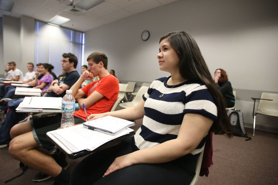 Sandrita Sanabria, a junior international student and international studies major, listens to assistant professor of political science Nicholas LaRowe as he begins his Introduction to American Politics class Tuesday in the Liberal Arts building.