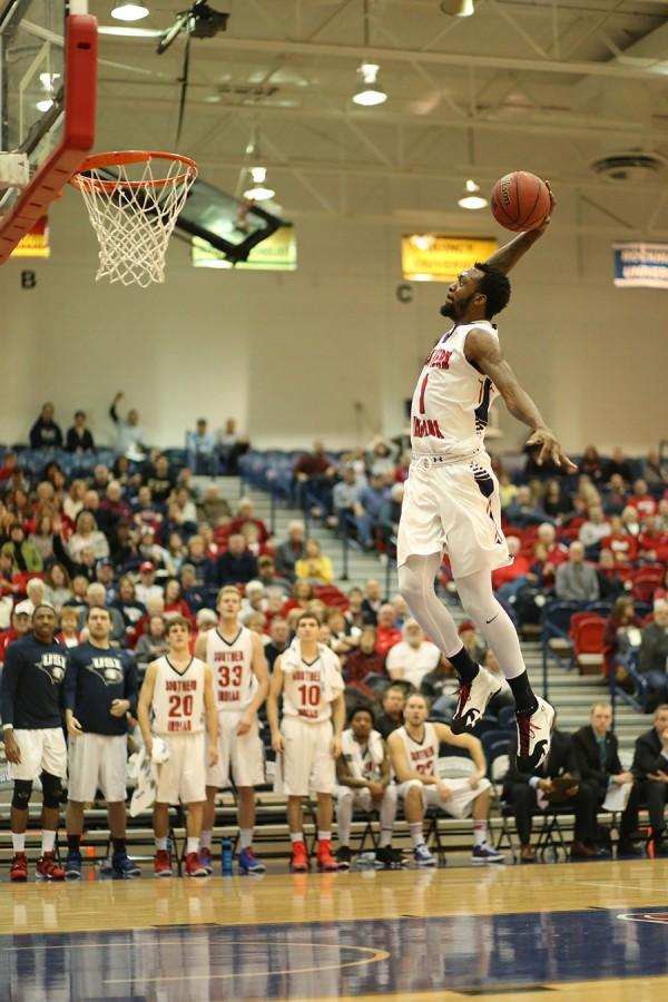 Junior guard Jeril Taylor leaps to dunk during the second half of the men's basketball game against Truman State University in the PAC.