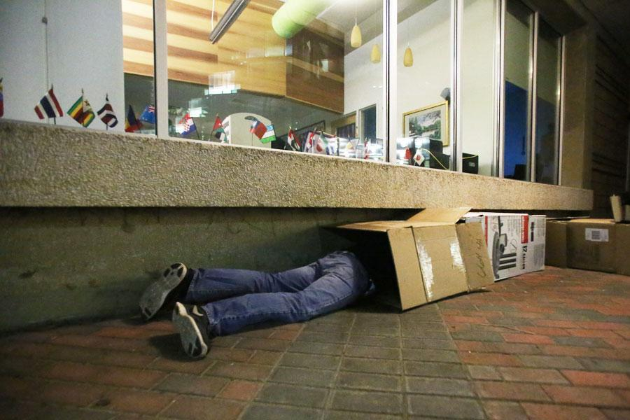 Seth Kidwell, a sophomore social work major, nestles into his newly constructed box home for the night Saturday outside of UC East. Kidwell was among 20 others who participated in Box Out of Boxville, an event organized to spread homelessness awareness by having students sleep in boxes overnight.