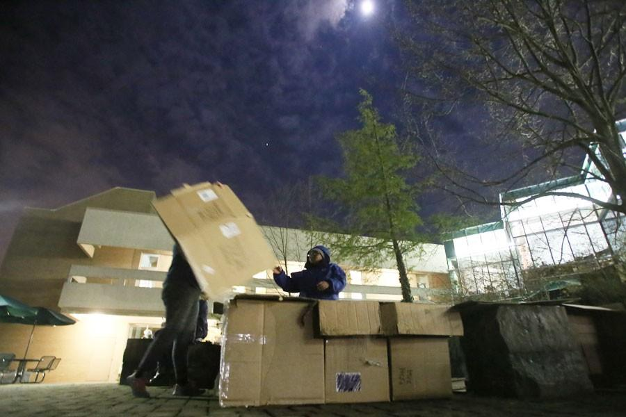 Sophomore chemistry major Sarah Hackman tosses a box over to senior social work major Danesha Shelton as they work together to build their box home for the evening Saturday outside of The University Center. Hackman, Shelton and several others planned to sleep in the boxes that night as they participated in Boxless.