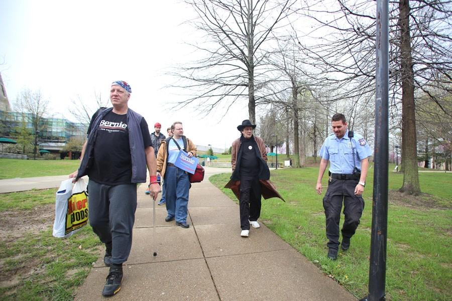 Public Safety officer Dustin Mellot escorts ralliers to the Free Speech Zone Thursday morning as they prepare to set up their presidential candidate Bernie Sanders stickers, brochures and posters.