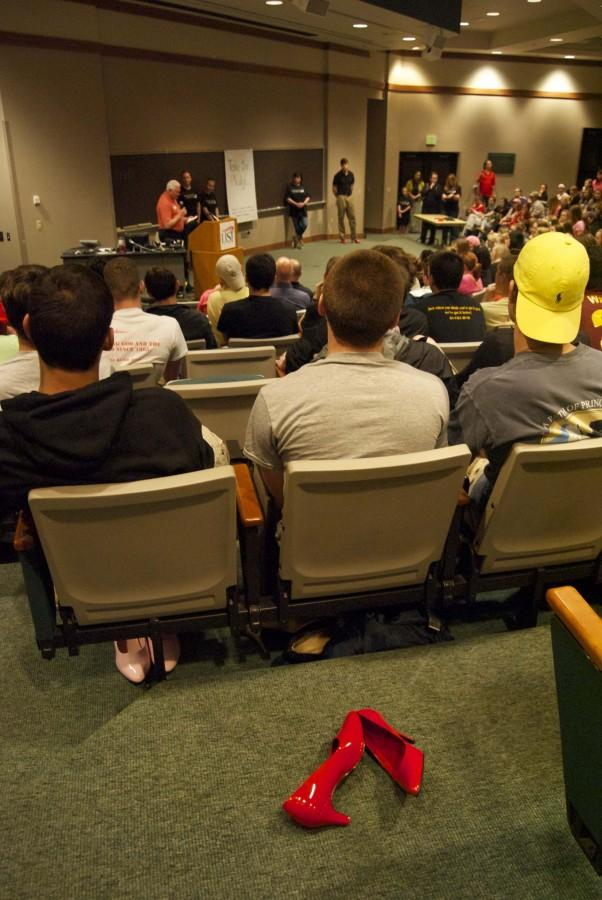 Students listen to a presentation in Mitchell Auditorium before donning colorful high heels and traipsing around campus during last year's Walk a Mile in Her Shoes.