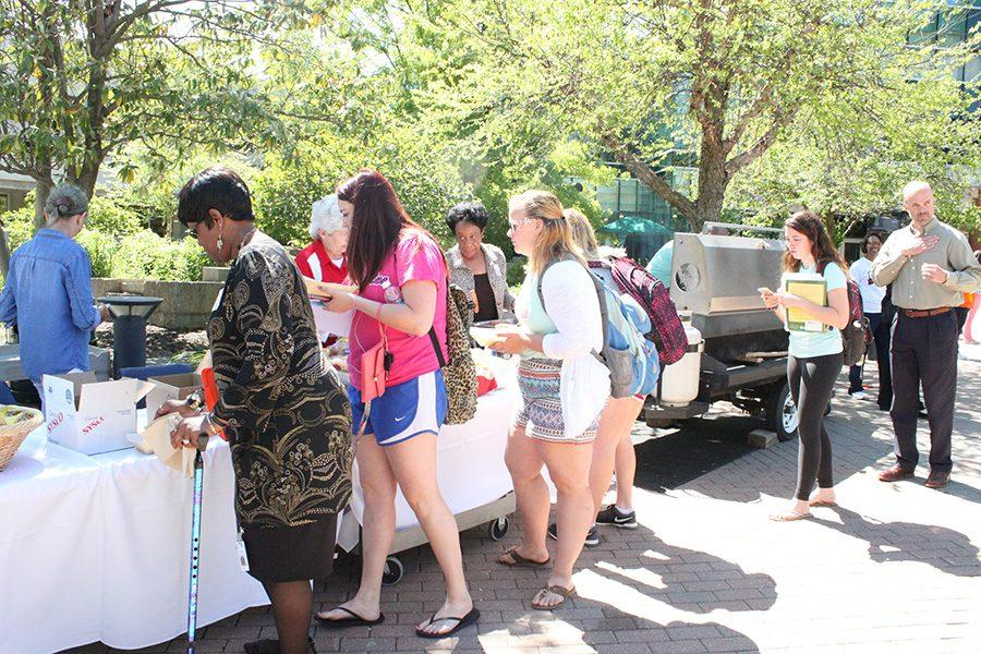 Students and faculty gather at the Amphitheatre to get complimentary drinks and food during the Stand Against Racism rally put on by the YWCA on Thursday.
