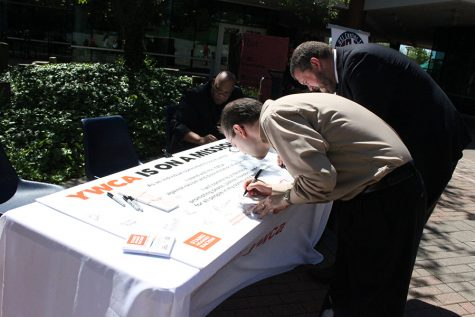 Dean of Students Brian Rush and counselor Thomas Longwell sign the poster which states that they will stand against racism or discrimination of any kind during the Stand Against Racism rally put on by the YWCA on Thursday.