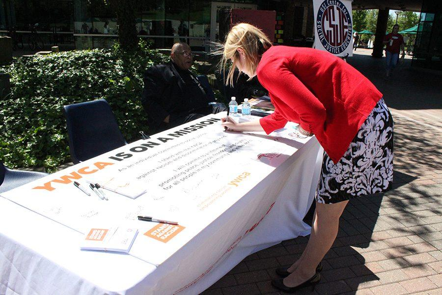 SGA president Ashley Wright signs the poster which vows to stand against racism or discrimination of any kind during the Stand Against Racism rally put on by the YWCA on Thursday.