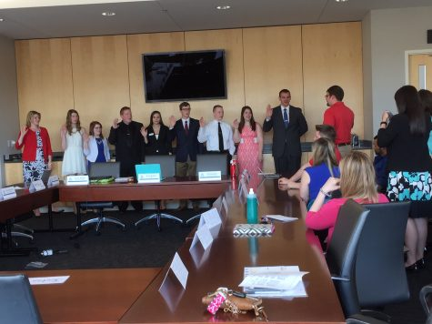 Chief Justice Jason Miner swears in the Student Government Association's '16-'17 members while '15-'16 President Alexa Bueltel takes a picture on her phone.