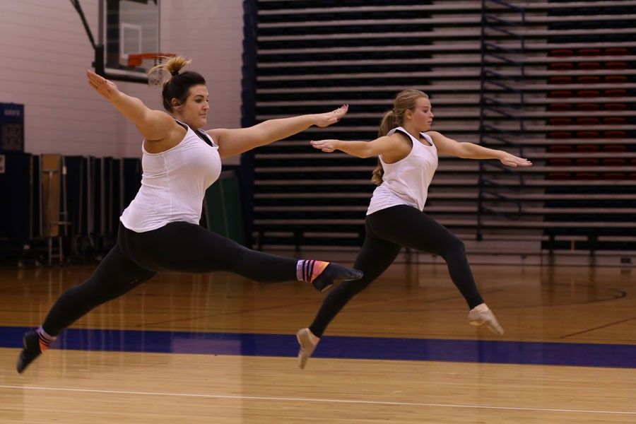 Senior psychology major Audrey Beckerle and junior nursing major Krista Zieg warm up with leaps at the beginning of dance team practice last October in the Physical Activities Center. The team will be competing in the National Dance Alliance College Nationals Thursday in Daytona, Florida.
