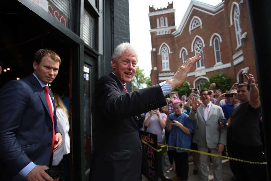 Former president Bill Clinton waves to the crowd Tuesday as he exits Penny Lane Coffee House, one of his two stops in Evansville.