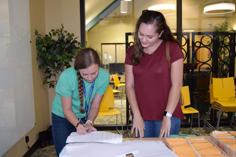 Senior+Housing+and+Residence+Life+worker+Megan+Sink+%28left%29+helps+freshman+business+major+Alicia+Fredrick+ready+paperwork+and+a+key+card+for+an+early+move-in+Aug.+16.