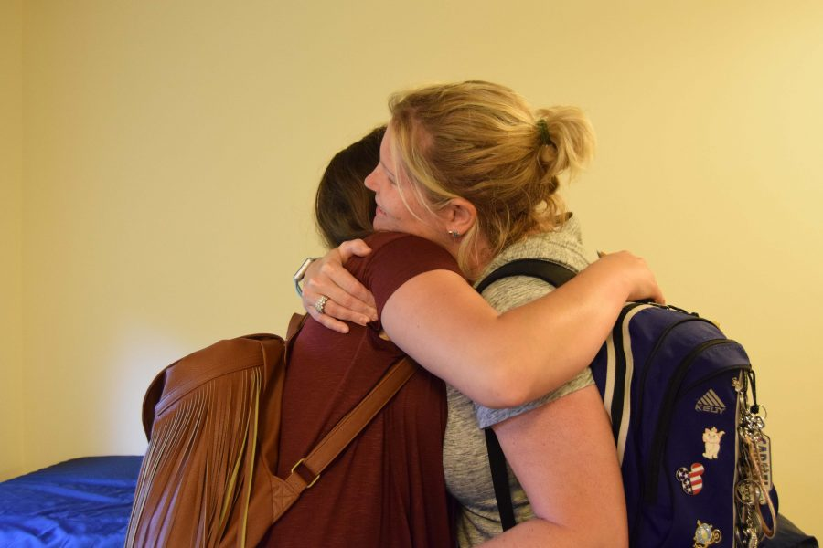 Fredrick and her mother embrace after moving Fredrick's belongings into her dorm. The two had seen pictures of the university but had never stepped foot on campus before move-in.