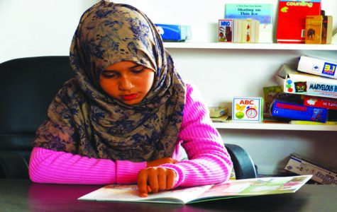 """A student studies at her school  library which was paid for by Road to Mafraq. The donations which funded the project were largely from the Evansville community. Elizabeth Riedford, an organizer for """"Run for Refugees,"""" said the girl told her her dream was to work hard to """"become just like her teacher."""""""