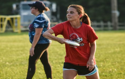 Brynne Dohery, a cutter on the women's ultimate frisbee team, throws a frisbee during an evening practice. The women's team started practices recently in preparation for their fall season.