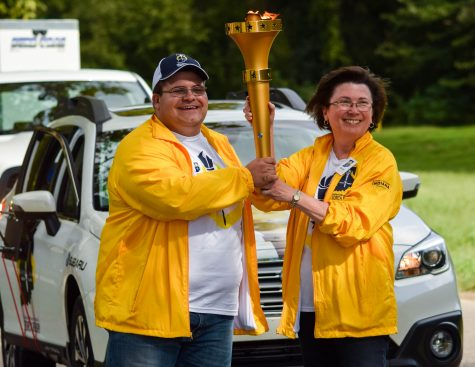 President Linda Bennett and USI alumni Cody Morris pass the torch at the Indiana Bicentennial Torch Relay.