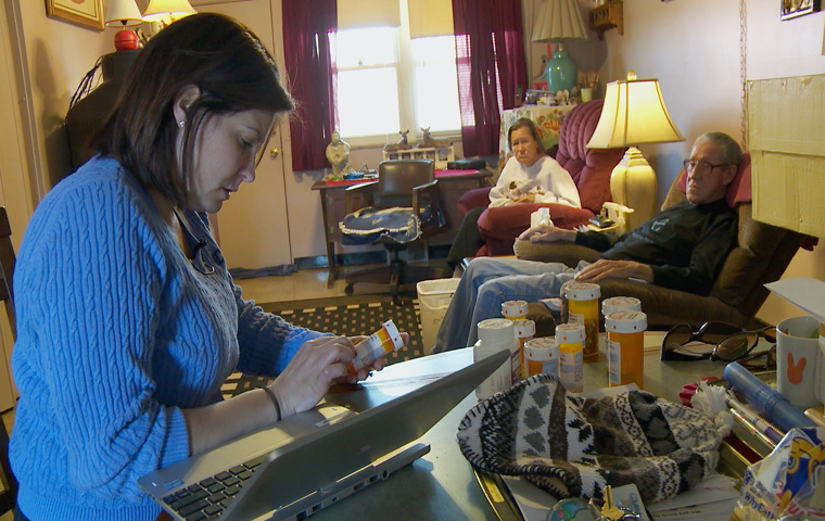 """Nurse practitioner Jessica MacLeod studies a prescription pill bottle in the home of Wink and Patty Sherill. The Sherill's are two of the subjects in """"The Invisible Patients."""" After being found without their prescriptions in their system they were no longer supported by their doctor."""