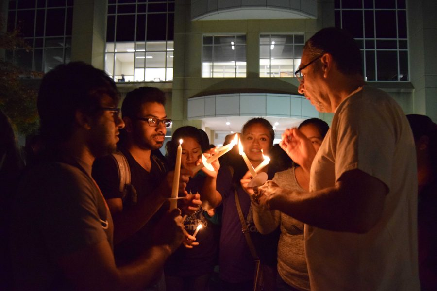 Spanish professor Manuel Apodaca-Valdez shares the flame of his candle with attendees at the university's celebration of the Day of the Dead. Apodaca-Valdez led students, faculty and visitors in a candlelight walk in front of the Liberal Arts Building, signifying the transition from life to the afterlife. The Day of the Dead celebration, put on by Student Government Association, Spanish Club and the Hispanic Student Union, has had about 100 attendees in past years.