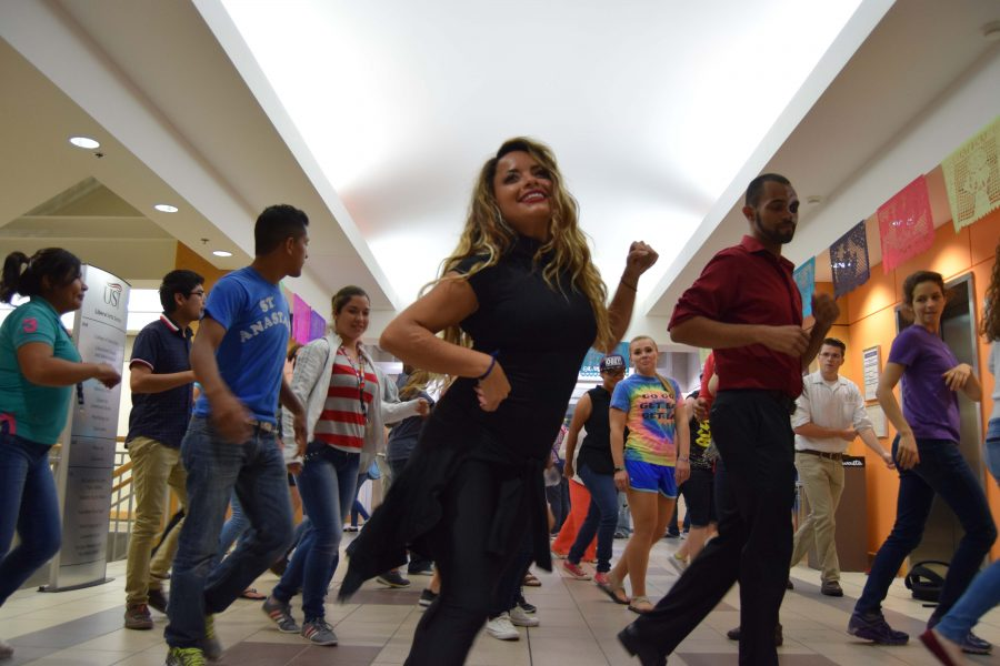 Local dance instructor Heidi Garza leads attendees at the university's Day of the Dead celebration in a salsa dance. The annual event featured Garza's Latin dance lessons as a new component of the three-hour celebration in the Liberal Arts Building.