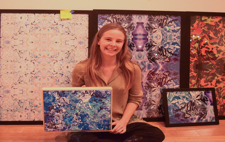 "Artist Jenna ""Citrus"" Reuger poses with some of her favorite artworks Monday afternoon in the McCutchan Art Center/Pace Gallery. Reuger has worked for a year on 130 pieces to put in the Efroymson Bridge Year Fellowship Exhibit."
