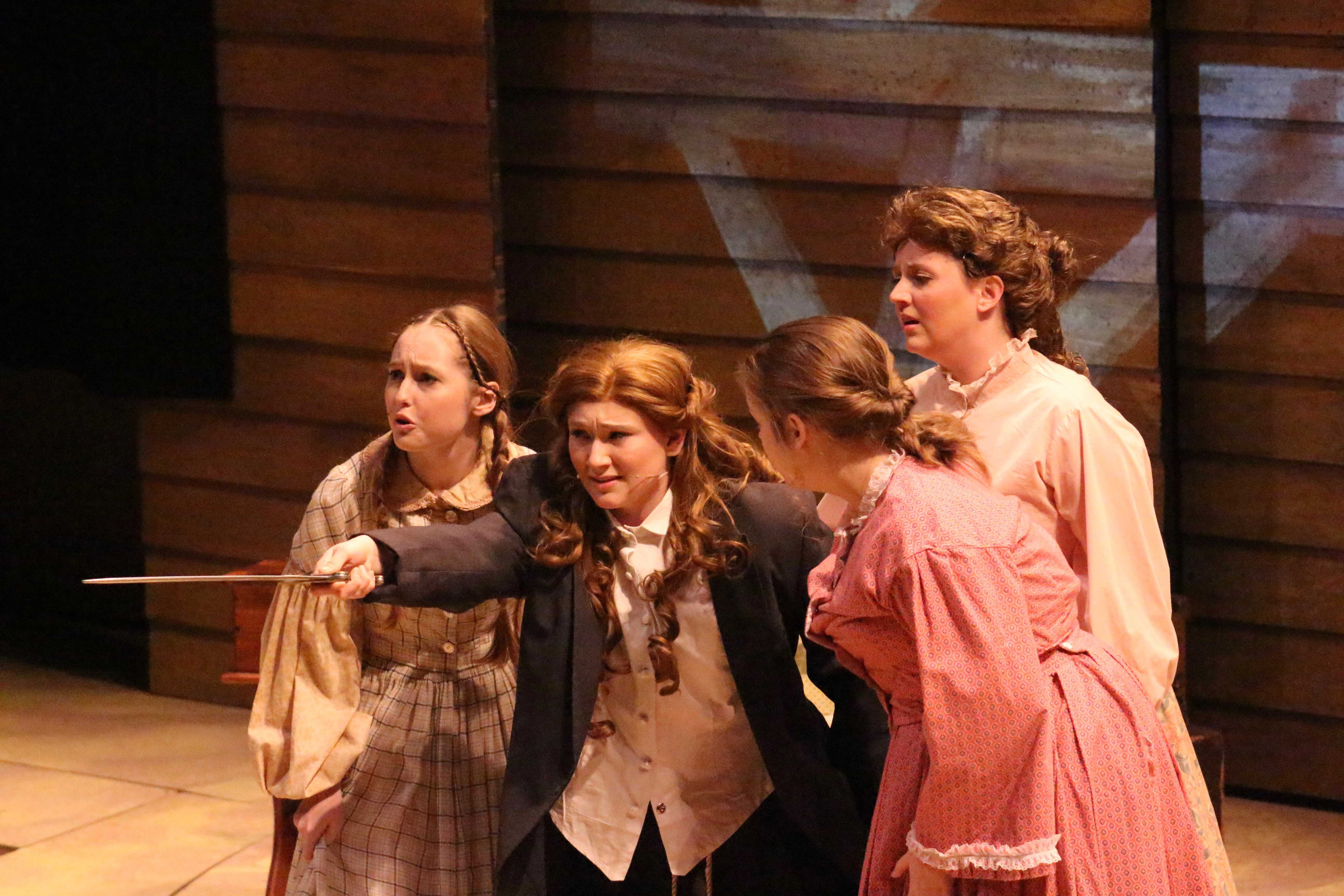 "Katie Jones (Amy March), Morgan Book (Meg March) and Maggie Browne (Beth March) huddle around Jacelyn Stewart (Jo March) as she tells them her plan to make everything better again for their family, during rehearsal for ""Little Women"" Tuesday evening in the Performance Center."