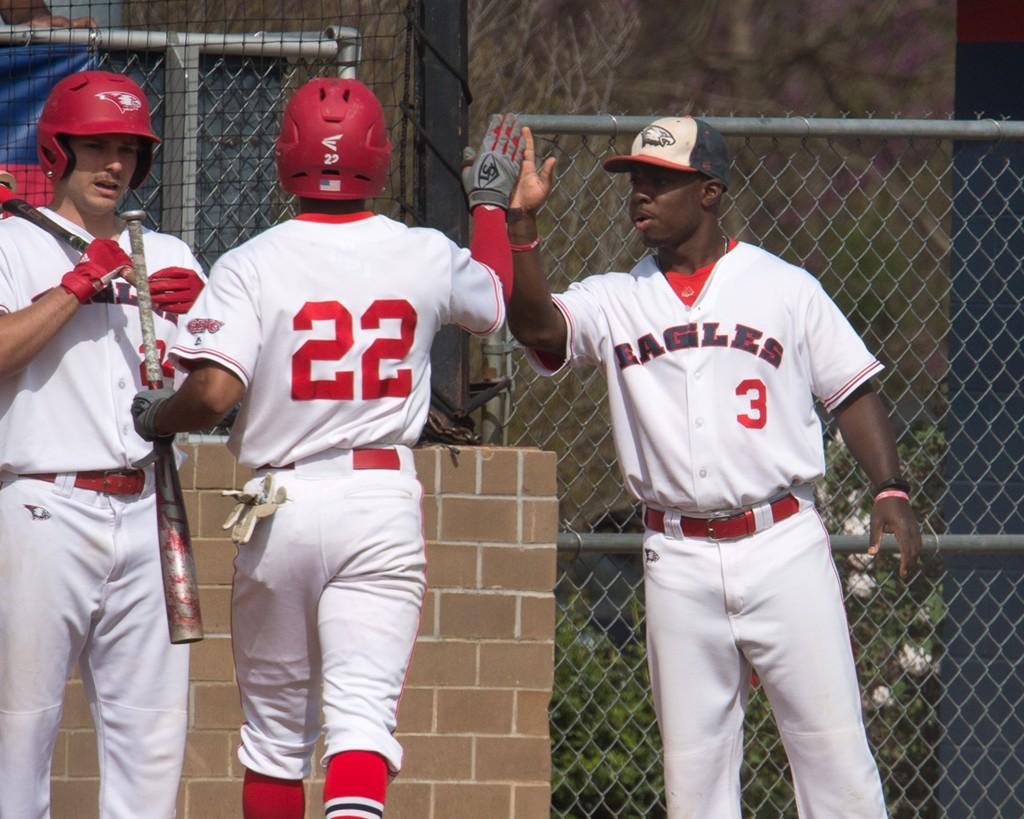 Senior Jaylen Quarles gives teammate Buddy Johnson a high-five after he walks off the field.