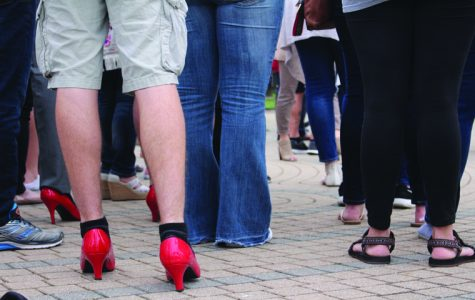 "After speeches about sexual assualt and gender violence, male audience members walked a mile in bright red high-heels to raise awareness for violence against women and men during the 11th annual ""Walk a Mile in Her Shoes"" Tuesday evening. Students, professors and community members walked from the UC, past the Orr Center and ended at the College of Liberal Arts, where members of the community, officers and Dean Beeby spoke about their experience walking in the heels, before the participants took a pledge to never ""commit, condone or remain silent about violence against women."""