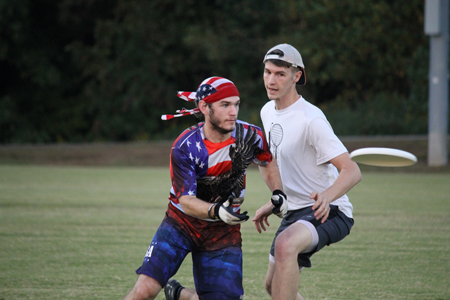 The men's ultimate Frisbee team begins its scrimmage with alumni during the 2015 season. Kyle Wood, alumni class of 2015, rushes to his teammates aid and attempts to catch his throw while Kyle Mayo, alumni class of 2012, swiftly tries to disrupt the play.
