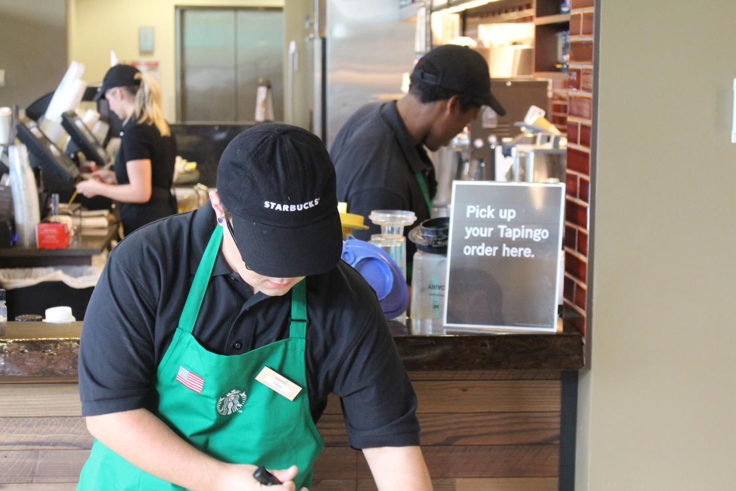 Sophomore social work major Clay Davis sweeps in front of the Tapingo pick-up counter at Starbucks. Tapingo is expected to bring delivery to the university in the fall of 2018