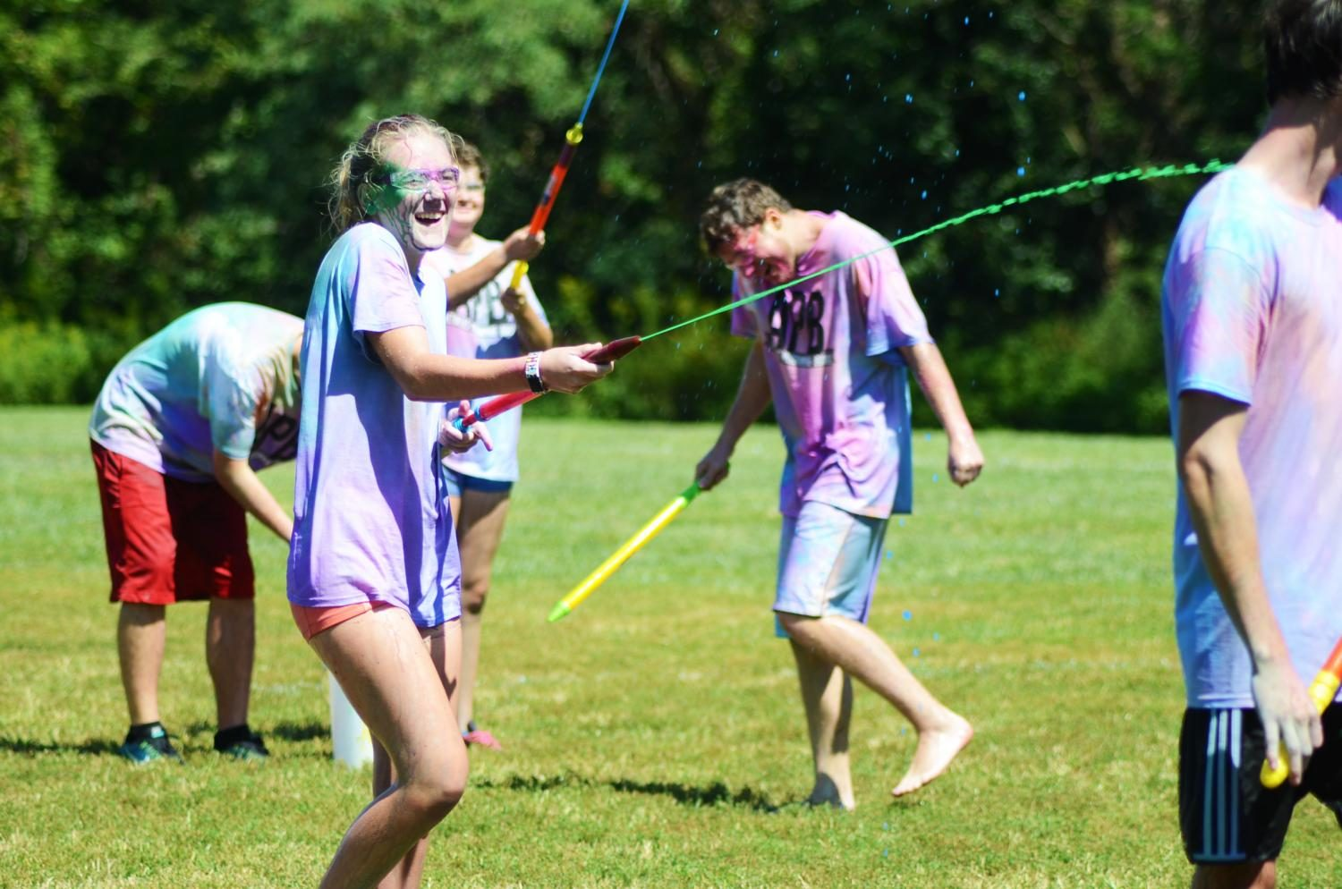 Freshman Paige Courtright ran through the rugby fields shooting paint at fellow students during the Paint War Sunday afternoon.
