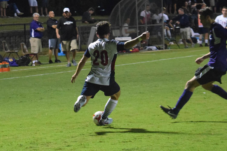 Ben Eklof, senior midfielder, clears the ball Thursday night.