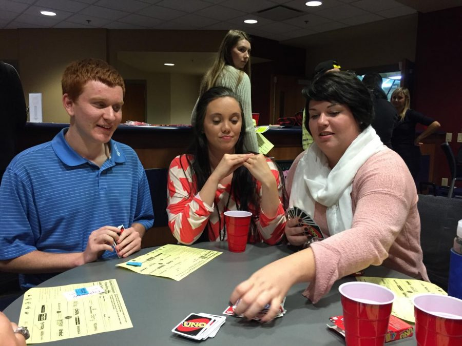 Marcus Gribbins (left) sophomore communication studies major, Hannah Holte (center) senior elementary and special education major, and Nicole Schwartz (right) a recruiter from T.J.Maxx played a challenging game of Uno at the networking game night Wednesday evening.