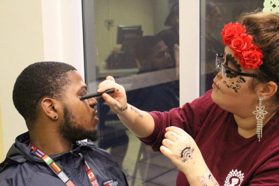 Theresa Holcomb, junior exercise science major, paints faces as a member of the art club for the Day of the Dead celebration Wednesday evening.