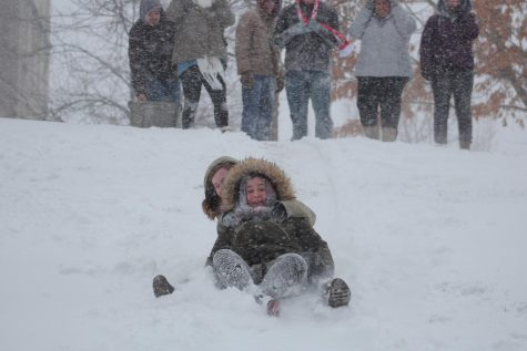 During a snow day on campus, freshmen english Major Emily McClusky and sociology major Emily Shipman sled down a hill located in between the Liberal Arts and the Romain College of Business building during the winter weather on January 12.