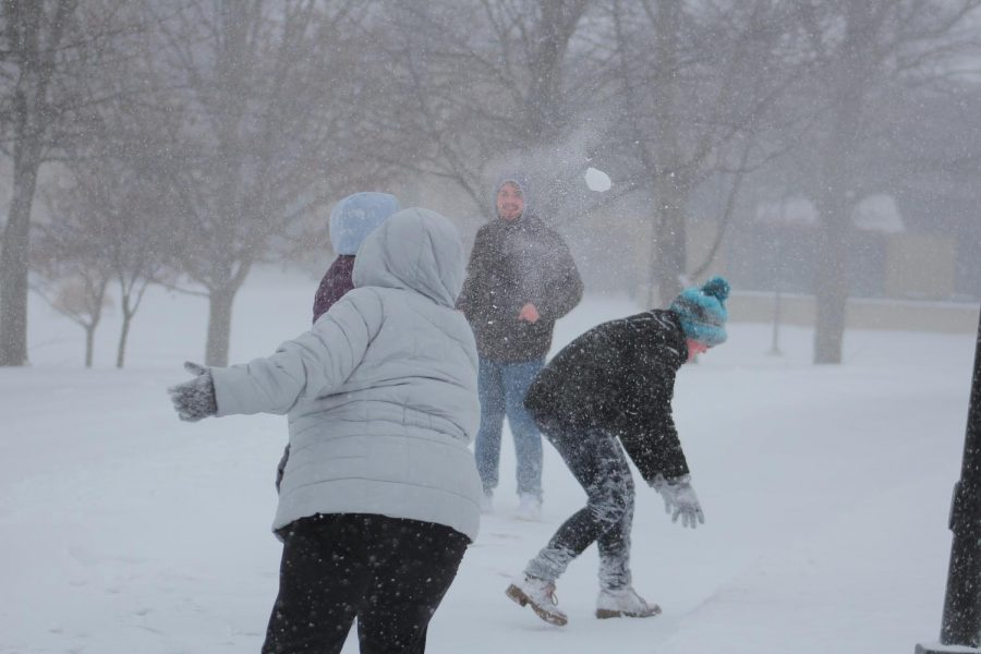 Freshman Ana Steensland throws a snowball at other students in a snowball fight when classes were canceled on Friday near the Public safety Building on January 12.