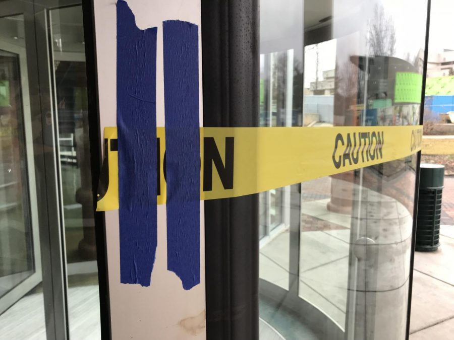 Duct tape holds together caution tape to the broken down revolving door in front of the Performance Center.