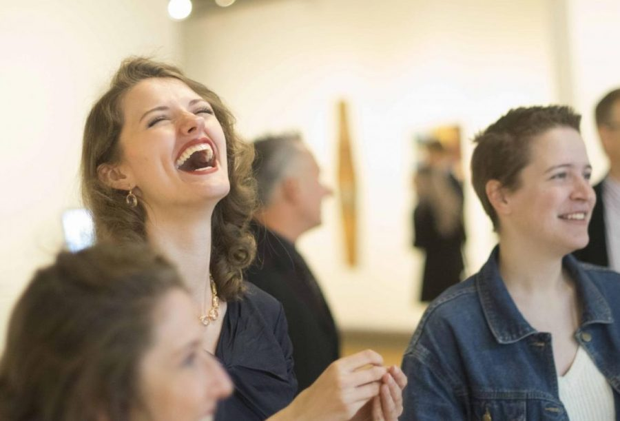 Sarah Feagan, a senior studio art major, laughs with friends during the Senior Seminar Exhibition Sunday afternoon. Feagan had two pieces accepted into the show.