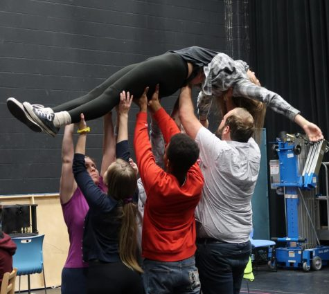 Cast members lift Christopher Boone during choreography.