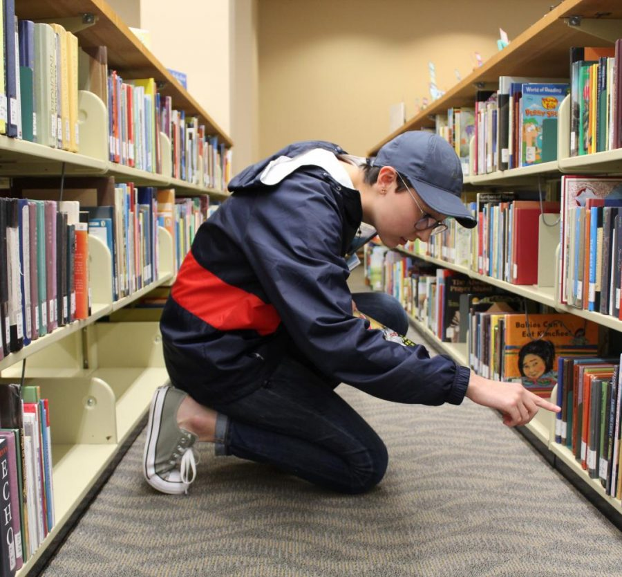 Holland Davis places books back where they belong at David L. Rice Library where she works part-time.