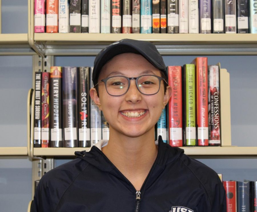 Holland Davis smiles in front of a stack of books in David L. Rice Library. Davis said she applied to work at the library because of her love for books.