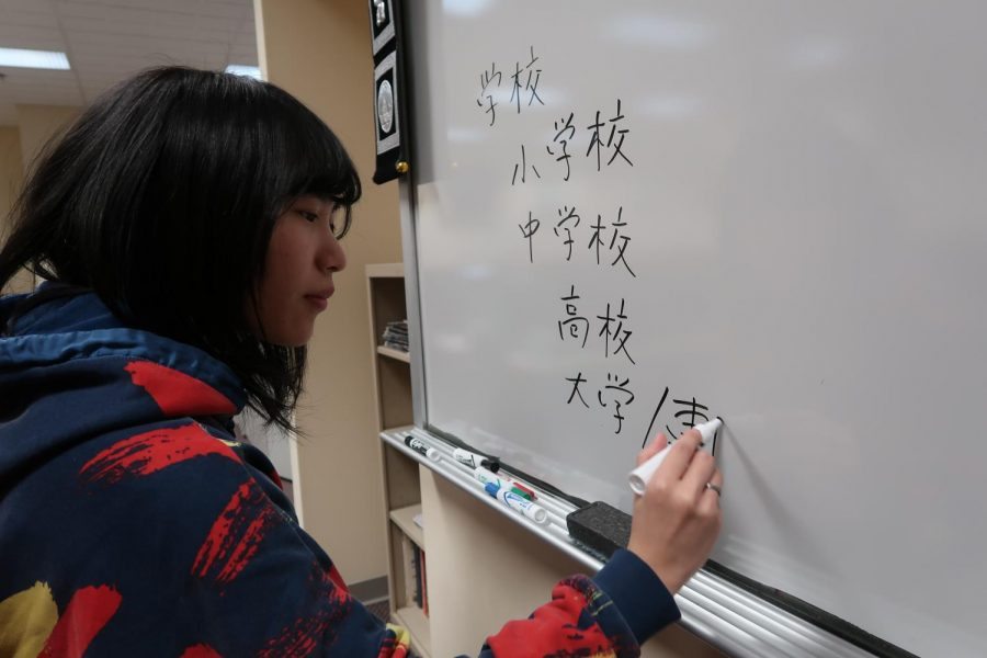 Shiho Hironaka, a first year graduate student studying second languages, writes Kanji on the board during a tutoring session.