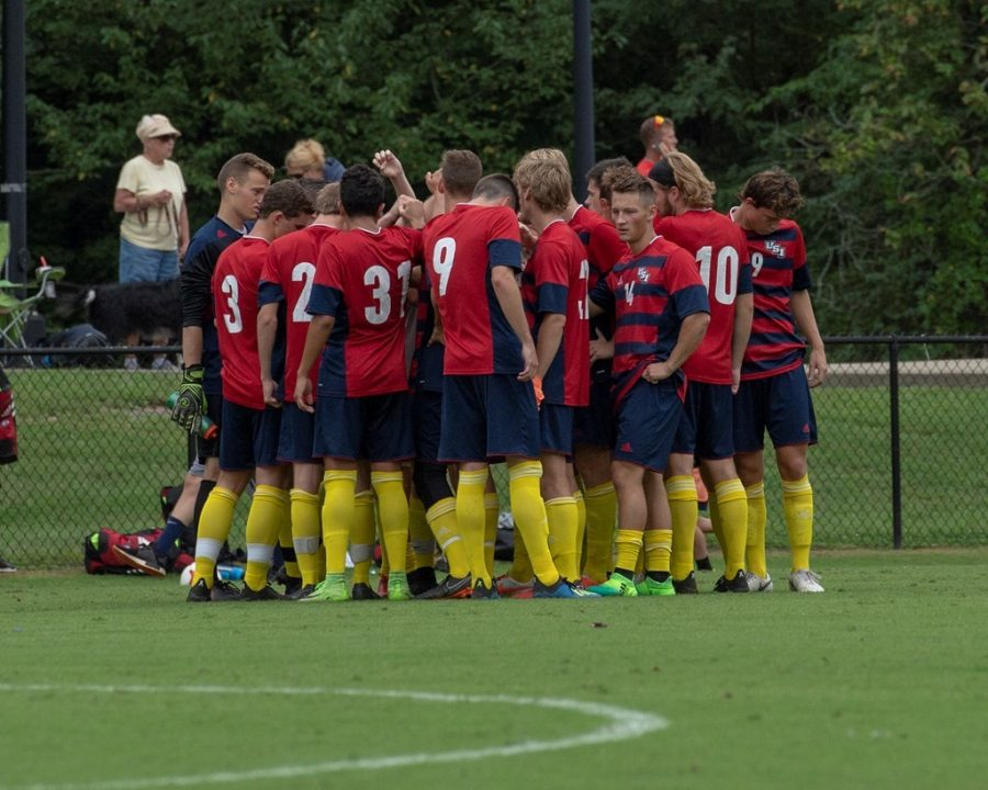 The men's soccer team huddles together during a game.