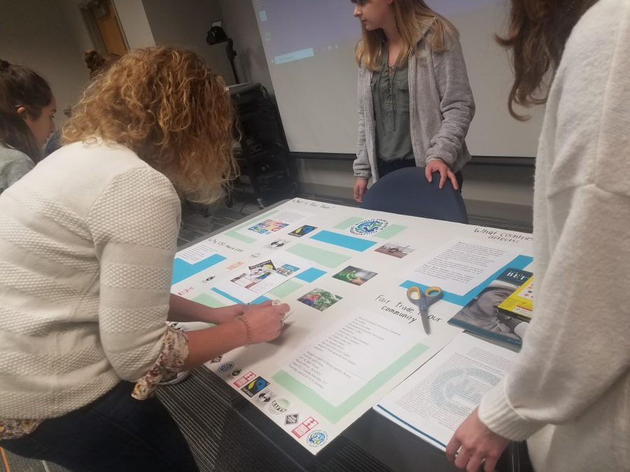 Students in global studies and political science instructor Ellen Topper's class work on a poster to spread awareness on fair trade.