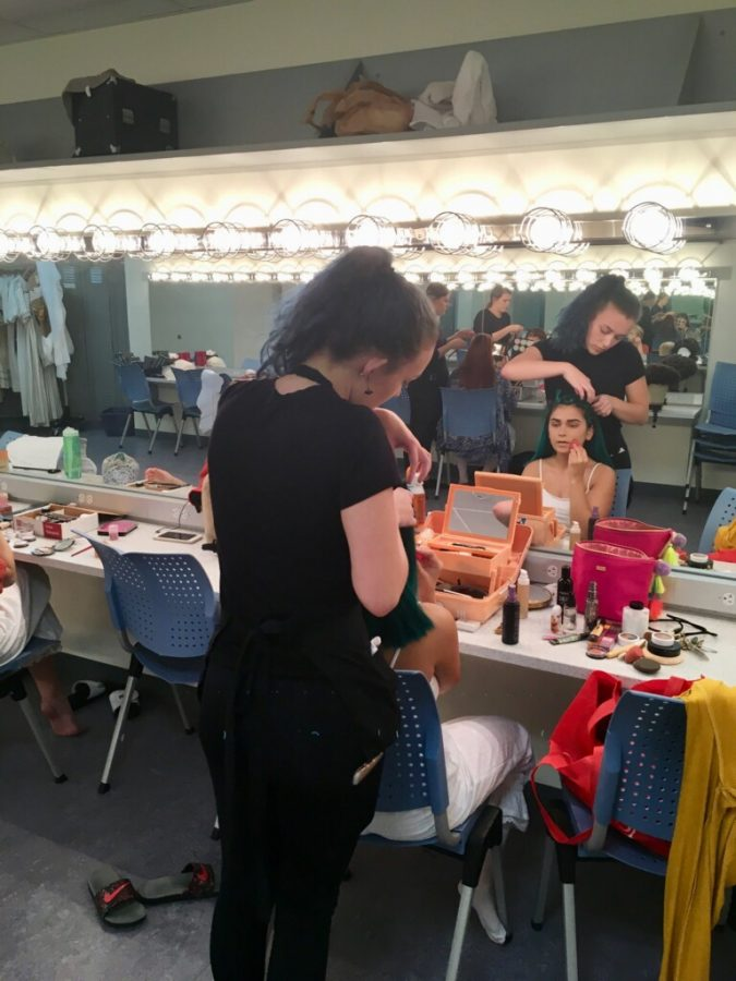 The wardrobe team helps the cast member with their costumes.