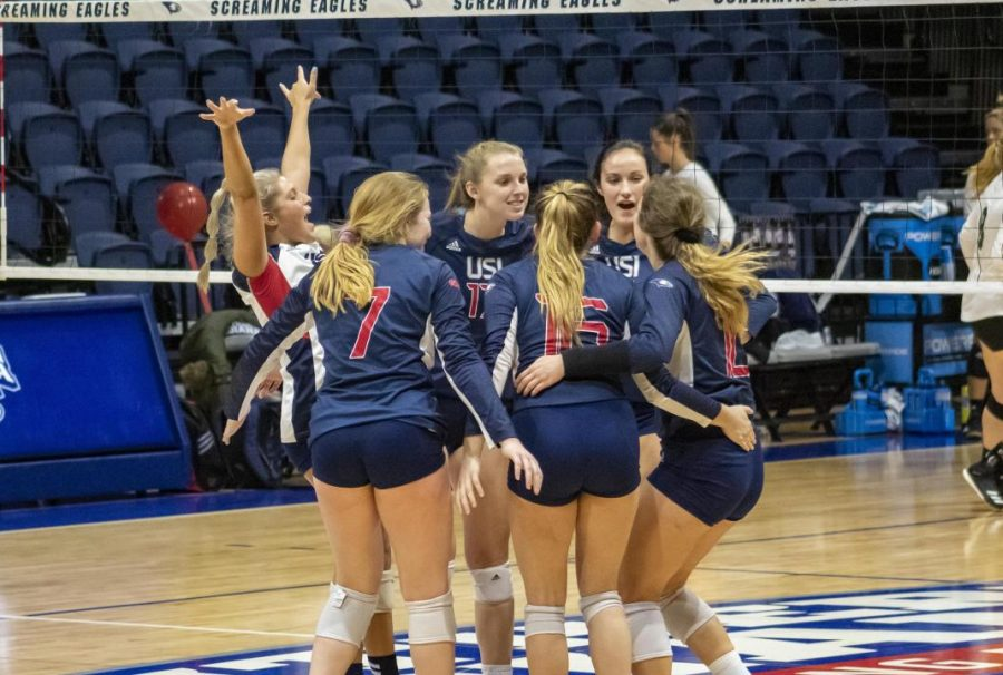 The women's volleyball team celebrate after scoring a point during Saturday afternoon's game. The eagles won 3-1 at Screaming Eagles Arena.